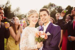 blowing-bubbles-for-newlyweds-outside-rustic-barn-wedding-venue