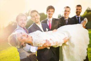 groomsmen-carrying-bride-outside-rustic-barn-wedding-venue
