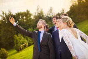 groomsmen-taking-selfie-outside-rustic-barn-wedding-venue