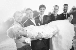 wedding-party-holding-bride-outside-rustic-barn-wedding-venue-greyscale