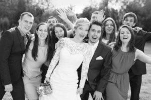 wedding-party-posing-outside-rustic-barn-wedding-venue-greyscale