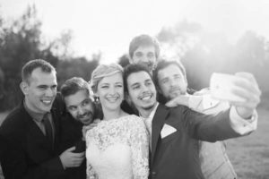 wedding-party-taking-selfie-barn-wedding-venue-greyscale